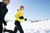 Two women jogging on snowy road, Styria, Austria