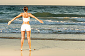 Adult, Adults, Alone, Back view, Beach, Beaches, Casual, Coast, Coastal, Color, Colour, Contemporary, Daytime, Exterior, Female, Fit, Fitness, Free, Freedom, Full-body, Full-length, Health, Healthy, Horizon, Horizons, Horizontal, Human, Informal, One, On