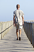 Adult, Adults, Alone, Back view, Beach, Beaches, Color, Colour, Contemporary, Daytime, Determination, Exterior, Footbridge, Footbridges, Full-body, Full-length, Future, Human, Leisure, Male, Man, Men, Men only, One, One person, Outdoor, Outdoors, Outside