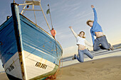 Couple jumping next to stranded fishing boat (Atlantic Ocean)
