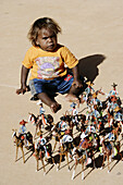 Child playing with small riders sculptures. Gunya Titjikala aborigine community. Northern Territory. Australia