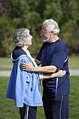 Active senior couple in exercise clothes embrace each other in an outdoor park.