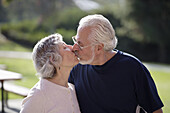 Portrait of active senior couple in exercise clothes kissing each other in an outdoor park.