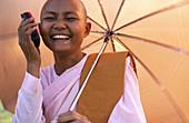 Nun with mobile. Myanmar (Burma)