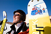 A man presenting his extra wide and decorated powder snow skis, Heliskiing, Kamchatka, Sibiria, Russia