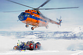 Helicopter picking up a group of skiers in snow, Heliskiing, Kamchatka Peninsula, Sibiria, Russia
