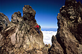 Mountaineer climbing over solidified lava spires, North Island, New Zealand