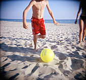 Amusement, Ball, Balls, Beach, Beaches, Color, Colour, Contemporary, Daytime, Exterior, Football, Fun, Holiday, Holidays, Horizontal, Human, Leg, Legs, Leisure, Outdoor, Outdoors, Outside, People, Person, Persons, Play, Playing, Recreation, Run, Running,