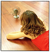 Woman liying down on the floor in front of a fan