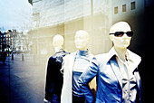 Cities, City, Clothing store, Color, Colour, Commerce, Daytime, Dressed up, Dummies, Dummy, Elegance, Elegant, Exterior, Fashion, Feminine, Glass, Horizontal, Lifeless, Lifelessness, Mannequin, Mannequins, Mirror image, Mirror images, Outdoor, Outdoors,