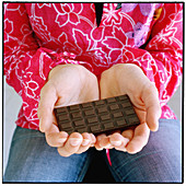 Adult, Adults, Aliment, Aliments, Chocolate, Chocolate bar, Chocolate bars, Close up, Close-up, Closeup, Color, Colour, Detail, Details, Female, Food, Hand, Hands, Hold, Holding, Human, Indoor, Indoors, Inside, Interior, Nourishment, One, One person, Peo