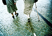 Adult, Adults, Anonymous, Back view, Cobble, Cobbles, Coblestone, Coblestones, Color, Colour, Companion, Companions, Contemporary, Crutch, Crutches, Daytime, Detail, Details, Difficult, Difficulty, Exterior, Female, Ground, Grounds, Health, Human, Mate,