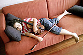 Alone, Barefeet, Barefoot, Bored, Boredom, Bow, Bows, Boy, Boys, Caucasian, Caucasians, Child, Child prodigy, Children, Closed eyes, Color, Colour, Contemporary, Couch, Couches, Dark-haired, Exhausted, Exhaustion, Facial expression, Facial expressions, H