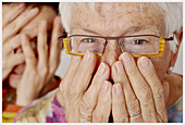 Adult, Adults, Afraid, Aged, Caucasian, Caucasians, Close up, Close-up, Closeup, Coering one s mouth, Color, Colour, Contemporary, Cover face, Cover mouth, Cover one s mouth, Covering face, Covering mouth, Elderly, Eyeglasses, Face, Faces, Facial express