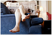 Adult, Adults, At home, Barefeet, Barefoot, Caucasian, Caucasians, Chill out, Chilling out, Color, Colour, Comfort, Comfortable, Contemporary, Couch, Couches, Economy, Feet, Female, Finance, Finances, Financial, Financial newspaper, Financial press, Foot