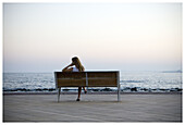 Adult, Adults, Back view, Bench, Benches, Blonde, Blondes, Coast, Coastal, Color, Colour, Contemporary, Daytime, Exterior, Fair-haired, Female, Horizon, Horizons, Human, Lean, Leaning, Lone, Loneliness, Lonely, Long hair, Long haired, Long-haired, One, O