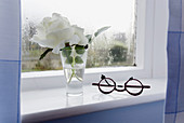 Detail of a window with eyeglasses and white rose