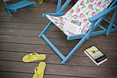 Adult, Adults, At home, Beach chair, Beach chairs, Book, Books, Calm, Calmness, Chill out, Chilling out, Color, Colour, Contemporary, Daytime, Deck chair, Deck chairs, Deckchair, Exterior, From above, Holiday, Holidays, Home, Leisure, Literature, Lying do