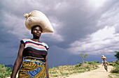 Women carrying heavy loads in their heads under stormy clouds on the trail to Tourou village (Goudours tribe from Nigeria) Mandara Mounts. Cameroon