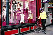 Biker in front of trendy underwear shop. London. England