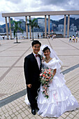 Just married couple on the waterfront promenade. Kowloon, Hong Kong. China