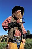 Bearded cowboy drinking coffee. M Lazy C Ranch, Colorado. USA