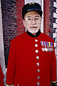 Pensioner in red uniform with medals, Chelsea Royal Hospital. London. England