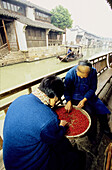 Women sorting red berries along the canal.Wushen, small historic city with many canals. Zhejiang province, China