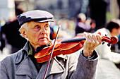 Elderly man playing violin at Charles Bridge. Prague. Czech Republic