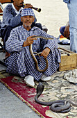 Snake charmer on Jemaa El-Fna square, the liveliest place night and day in Marrakech. Morocco.