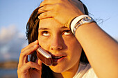 16 years old teenager talking on a mobile phone. Hendaye beach. Aquitaine. France.
