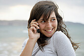 16 year old teengirl using cell phone at beach