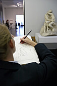 Young woman drawing The Kiss, by Auguste Rodin, Tate Modern. London. England. UK.