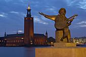 Sculpture of a musician on Riddarholmen and view onto the Stadshuset on Kungsholmen, Stockholm, Sweden