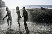 Teenagers under a waterfall. Mayotte, island of the Comoros archipelago in the Indian Ocean, French territory.
