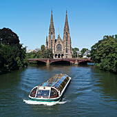 Sightseeing boat and St. Paul church in background. Strasbourg. France