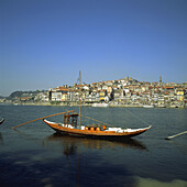 Rabelos boats. Port wine transportation boat on Douro river and town skyline. Porto. Portugal.