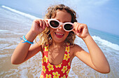 Amusement, Amusing, Bathing suit, Bathing suits, Beach, Beaches, Blonde, Blondes, Carefree, Caucasian, Caucasians, Child, Children, Children only, Coast, Coastal, Color, Colour, Contemporary, Daytime, Exterior, Eyeglasses, Facial expression, Facial expre