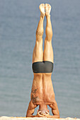 Adult, Adults, Back view, Balance, Beach, Beaches, Calisthenics, Callisthenics, Color, Colour, Concentrate, Concentrating, Concentration, Contemporary, Daytime, Equilibrium, Exercise, Exercises, Exterior, Fit, Full-body, Full-length, Handstand, Handstand