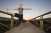 Man Doing a Leg Stretch on Footbridge