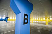 Blau, Buchstabe, Buchstabe B, Buchstaben, Farbe, Garage, Garagen, Gelb, Innen, Konzept, Konzepte, Leer, Menschenleer, Niemand, Parkhaus, Parkhäuser, Parking, Parkplatz, Parkplätze, Säule, Säulen, Schild, Schilder, Tageszeit, C38-623522, agefotostock