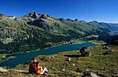 Couple sitting on alpine pasture, Lake Silvaplaner and Lake Champfer, Engadin, Grisons, Switzerland