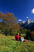 Couple resting on alpine pasture, Kaiser range in background, Wilder Kaiser range, Tyrol, Austria