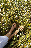 Anonymous, Color, Colour, Contemporary, Country, Countryside, Daisies, Daisy, Daytime, Detail, Details, Exterior, Female, Flower, Flowers, Human, Lying down, Outdoor, Outdoors, Outside, People, Person, Persons, Rural, Sandal, Sandals, Shoe, Shoes, Vertic