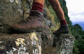 Hiking boots, man climbing onto Mt. Gower, Lord Howe Island, Australia