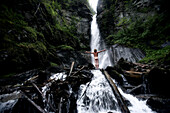 Naked young man standing in front of a waterfall, See, Tyrol, Austria