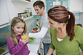 Family in kitchen, daughter drinking a glass of juice, Munich, Germany