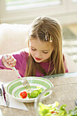 Girl (3-4 years) eating salad, Munich, Germany