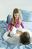 Father and daughter (3-4 years) playing on bed, Munich, Germany