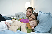 Young family lying on bed, mother and daughter sleeping, Munich, Germany